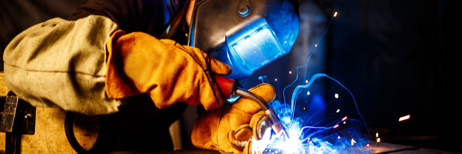 Worker cutting metal with plasma equipment. on plant