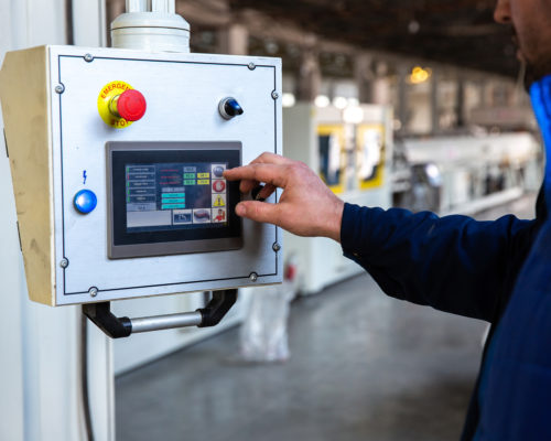 worker uses control panel in factory